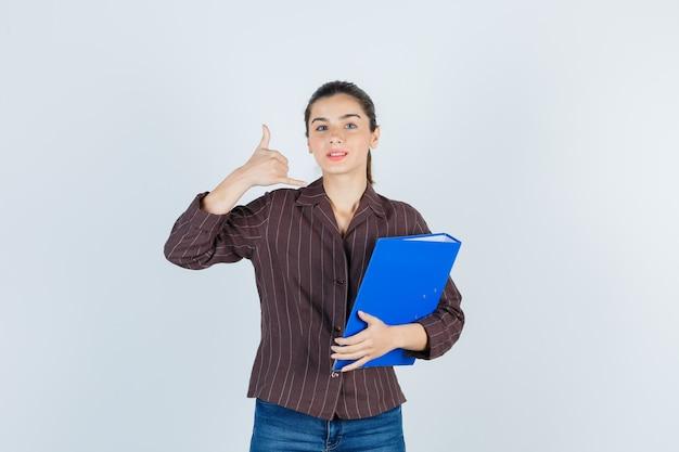フォルダーを保持し、シャツ、ジーンズで電話のジェスチャーを示し、物欲しそうな正面図を探している若い女性。
