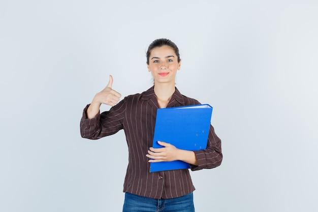 フォルダーを保持している若い女性、シャツ、ジーンズで親指を表示し、満足そうに見える、正面図。