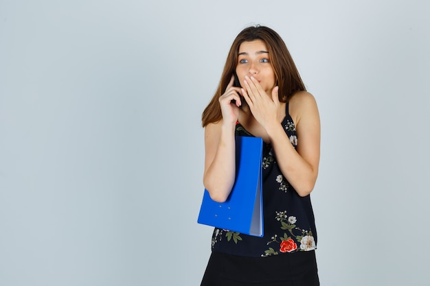 Young lady holding folder, talking on mobile phone, keeping hand on mouth in blouse, skirt and looking excited. front view.