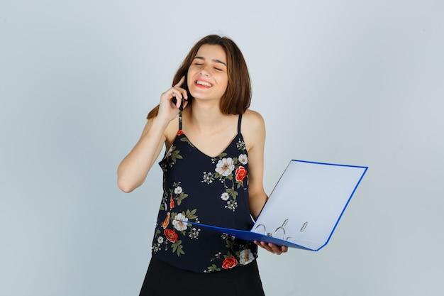 Молодая леди, держащая папку, разговаривает по мобильному телефону в блузке и выглядит веселой, вид спереди.