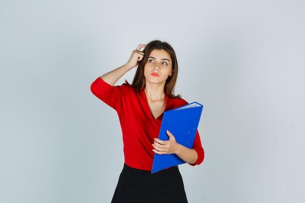 Девушка в красной блузке, юбке и задумчиво смотрит в руку, держа папку и почесывая голову