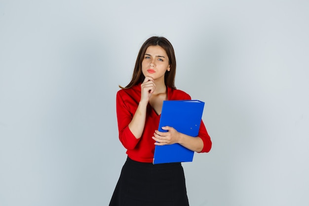 Young lady holding folder while standing in thinking pose in red blouse