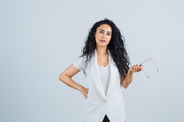 흰색 티셔츠, 재킷을 입은 안경을 들고 자신감을 보이는 젊은 여성. 전면보기.