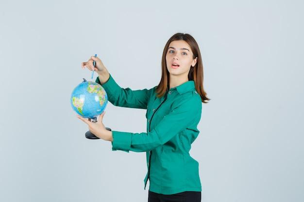 地球儀を持ってシャツを着てそれを指差して困惑している若い女性、正面図。