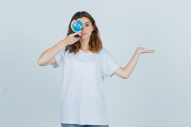 Tシャツ、ジーンズ、自信を持って何かを見せながら、目の近くに地球儀を持っている若い女性。正面図。