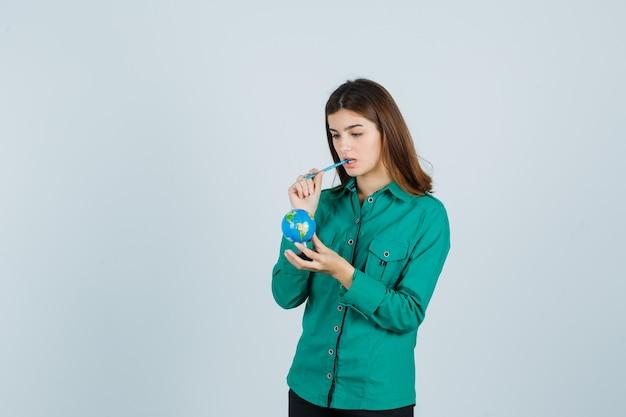 シャツにペンを口に入れて物思いにふけるように見ながら地球儀を保持している若い女性。正面図。