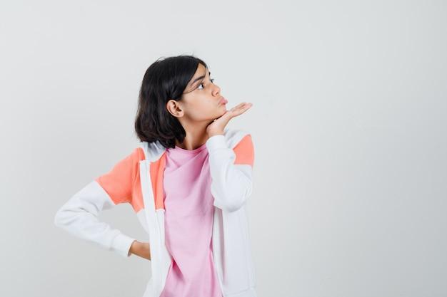 ジャケット、ピンクのシャツを脇に見て、奇妙に見える間、彼女の顎に手をつないでいる若い女性。
