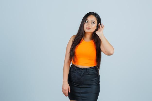 一重項、ミニスカートで耳の後ろに手を握り、集中して見える若い女性。正面図。