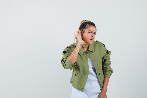 Tシャツジャケットで耳の後ろに手をつないで好奇心旺盛な若い女性