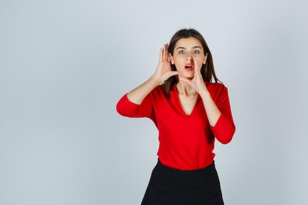 赤いブラウスで秘密を語りながら耳の後ろで手をつないでいる若い女性