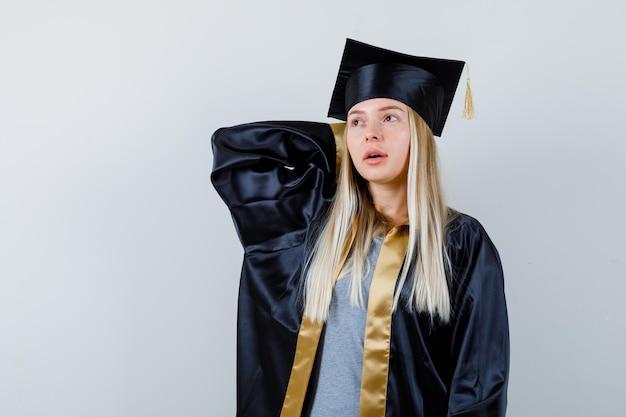 アカデミックドレスを着て頭の後ろで手を握り、集中して見える若い女性。