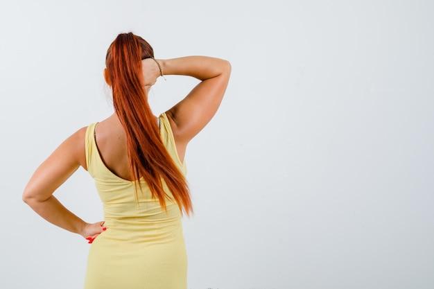 黄色のドレスを着て頭の後ろで手をつないで、焦点を当てて、背面図を探している若い女性。