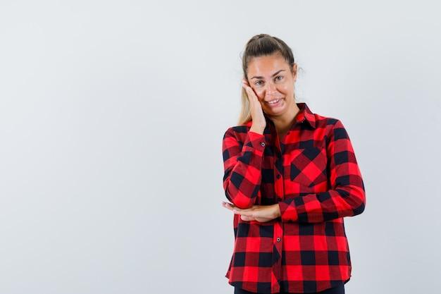 Giovane donna che tiene la mano sulla guancia in camicia a quadri e sembra sognante