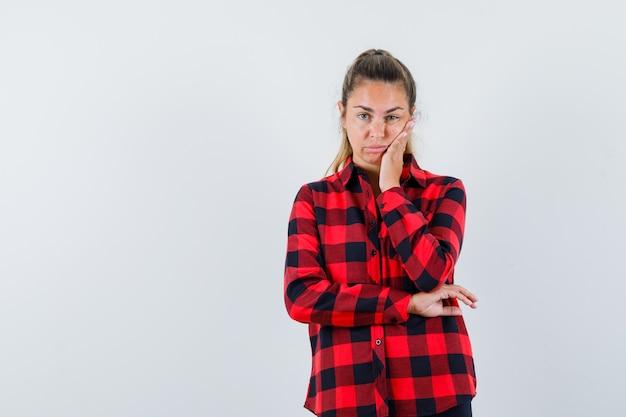Giovane donna che tiene la mano sulla guancia in camicia a quadri e sembra senza speranza
