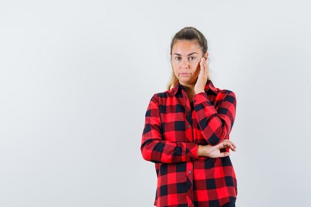 Giovane donna che tiene la mano sulla guancia in camicia a quadri e sembra ragionevole