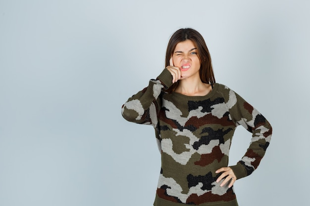 Giovane donna che tiene la mano sulla guancia in maglione e sembra aggressiva