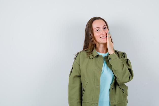 Giovane donna che tiene la mano sulla guancia in t-shirt, giacca e sembra carina, vista frontale.