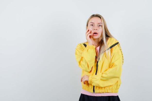 Giovane donna che tiene la mano sulla guancia in t-shirt, giacca e guardando perplesso