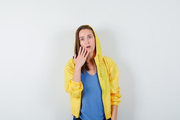 Giovane donna che tiene la mano sulla guancia in maglietta, giacca e sembra sorpresa