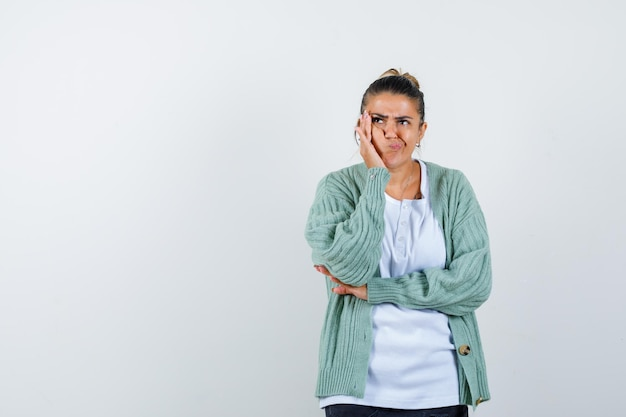 Giovane donna che tiene la mano sulla guancia in maglietta, giacca e sembra pensierosa