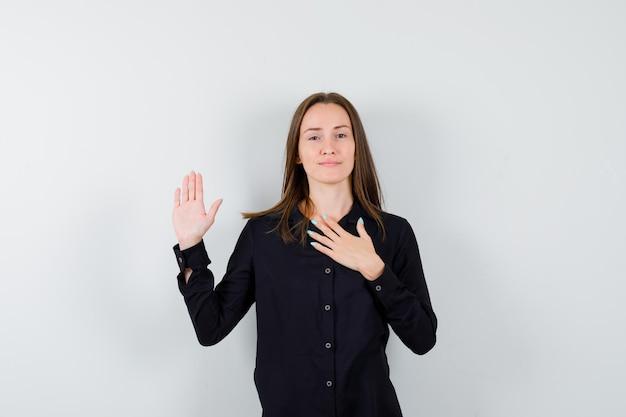Giovane donna che tiene la mano sul petto e mostra il palmo