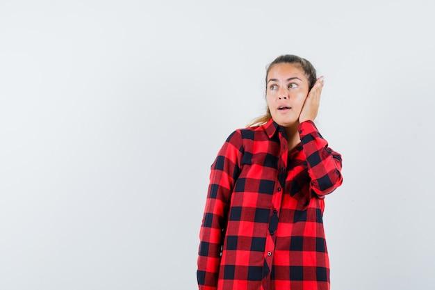 Giovane donna che tiene la mano sull'orecchio in camicia a quadri e sembra carino