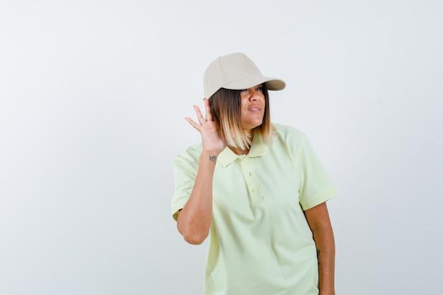 Giovane donna che tiene la mano dietro l'orecchio in t-shirt, berretto e guardando concentrato. vista frontale.