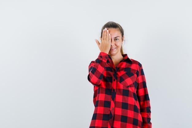 Giovane donna che tiene la mano sull'occhio in camicia a quadri e sembra allegra