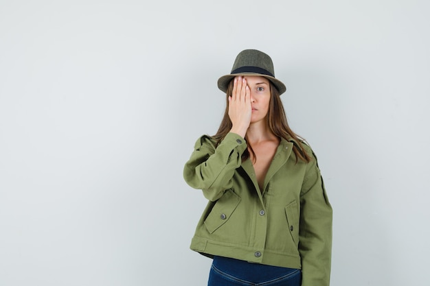 Young lady holding hand on eye in jacket pants hat and looking calm