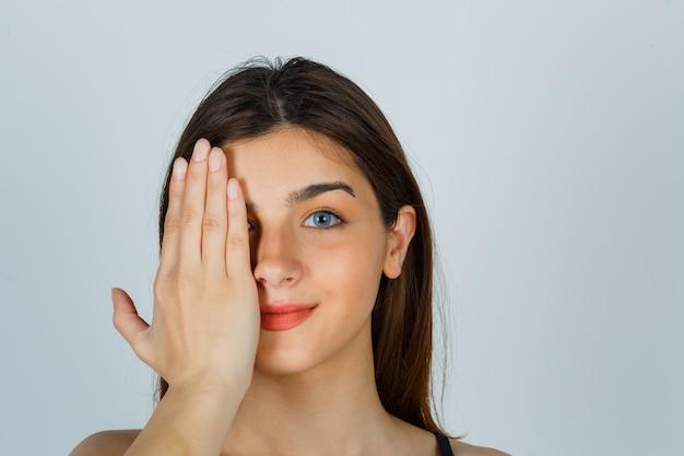 Giovane donna che tiene la mano sull'occhio e sembra allegra. vista frontale.