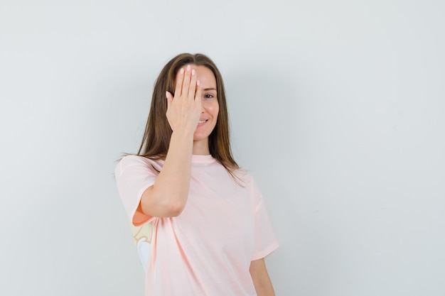Young lady holding hand on eye in pink t-shirt and looking cheery
