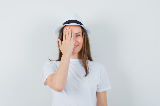 Young lady holding hand on eye in white t-shirt hat and looking cheery
