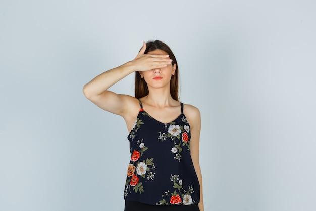 Giovane donna che tiene la mano sugli occhi in camicetta e sembra spaventata, vista frontale.