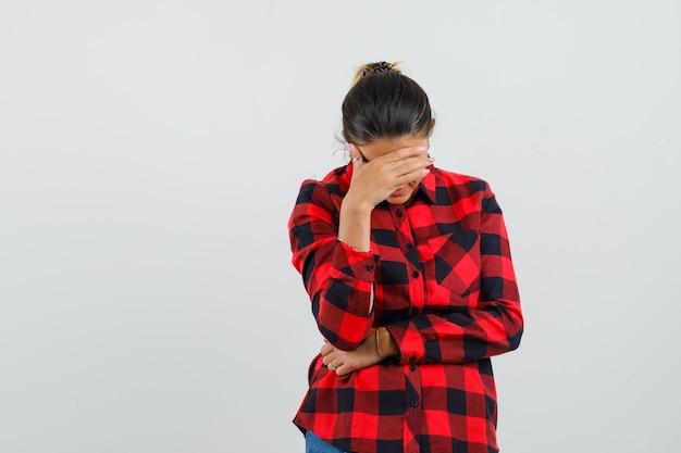 Giovane donna che tiene la mano sopra gli occhi in camicia a quadri e sembra imbarazzata