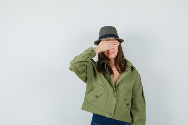 Young lady holding hand on eyes in jacket pants hat and looking optimistic