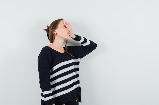 Giovane donna che tiene la mano sul viso in camicia casual e sembra stanco