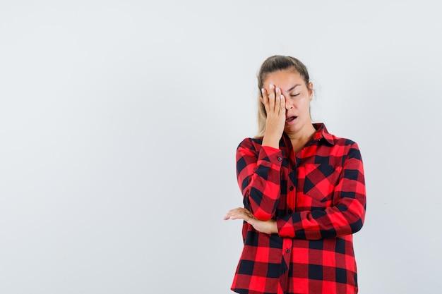 Giovane donna che tiene la mano sul viso in camicia a quadri e sembra assonnato