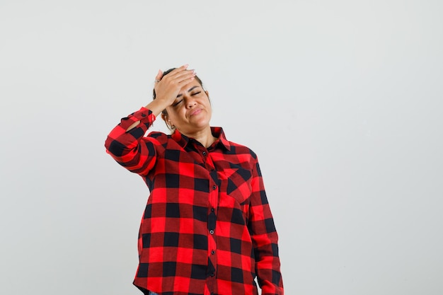 Young lady holding hand on forehead in checked shirt and looking forgetful