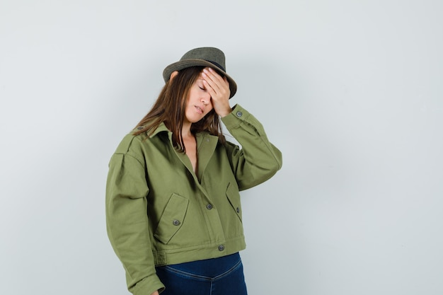 Young lady holding hand on forehead in jacket pants hat and looking depressed