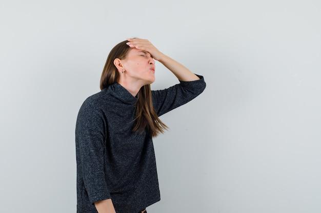 Giovane donna che tiene la mano sulla fronte in camicia e sembra smemorato