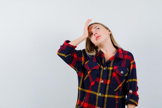 Giovane donna che tiene la mano sulla fronte mentre cerca in camicia a quadri e sembra pensierosa. vista frontale.