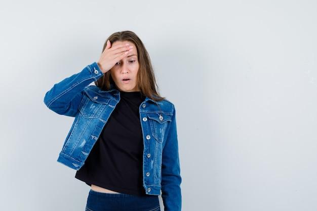 Giovane donna che tiene la mano sulla testa in camicetta, giacca e sembra smemorata, vista frontale.