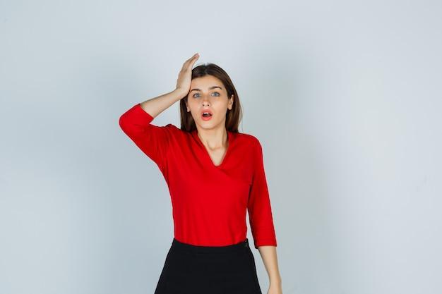 Giovane donna che tiene la mano sulla testa in camicetta rossa, gonna e sguardo smemorato