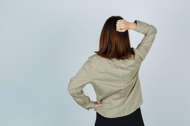 Giovane donna che tiene la mano dietro la testa in camicia, gonna e guardando pensieroso, vista posteriore.