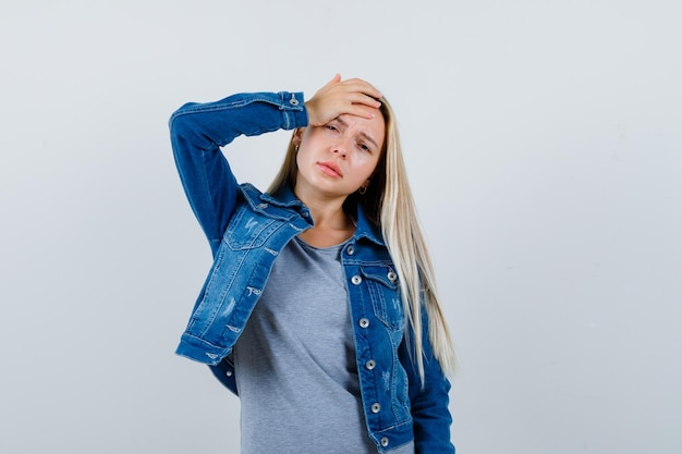 Young lady holding hand on head in t-shirt, denim jacket, skirt and looking tired
