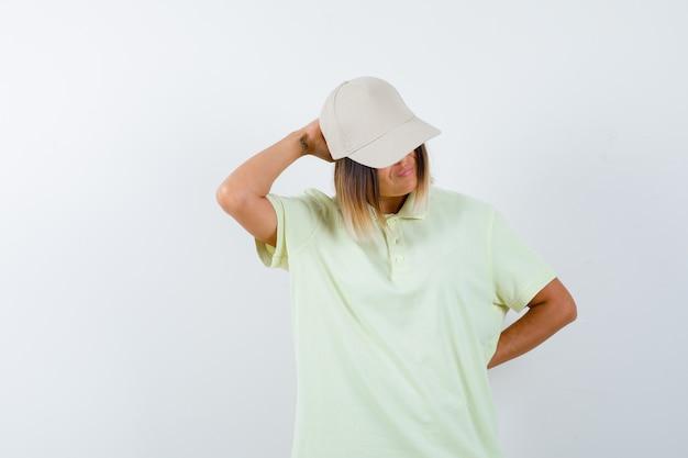 Giovane donna che tiene la mano sulla testa mantenendo la mano dietro la schiena in t-shirt, berretto e guardando pensieroso. vista frontale.