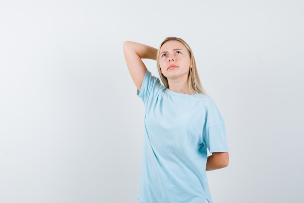 Young lady holding hand behind head while looking up in t-shirt and looking thoughtful. front view.