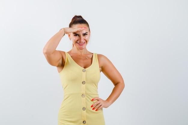 Giovane donna che tiene la mano sopra la testa in abito giallo e sembra allegra. vista frontale.