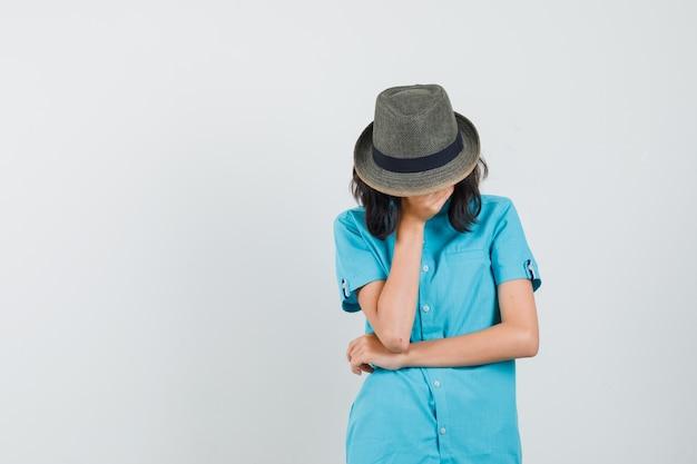 Giovane donna che tiene la mano sul viso in camicia blu, cappello e sguardo sconvolto.