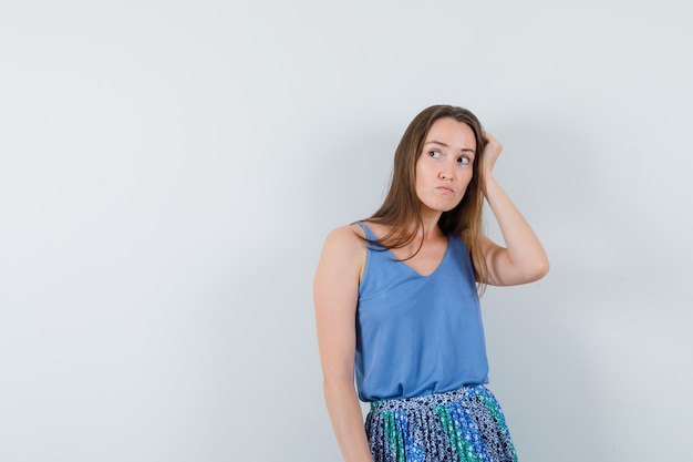 Young lady holding hand on her head in blouse,skirt and looking displeased , front view. space for text